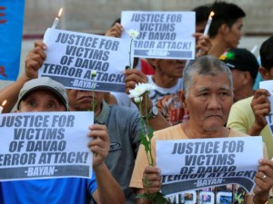 Rallyists display placards condemning the bombing at a market in Davao city during a candlelight protest in front of the Catholic church in Quiapo city, metro Manila. Photo: Reuters